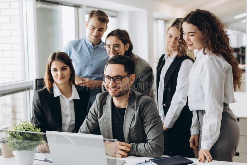 Mitarbeiter, die einen Computer betrachten und über Arbeit sprechen lizenzfreie stockbilder