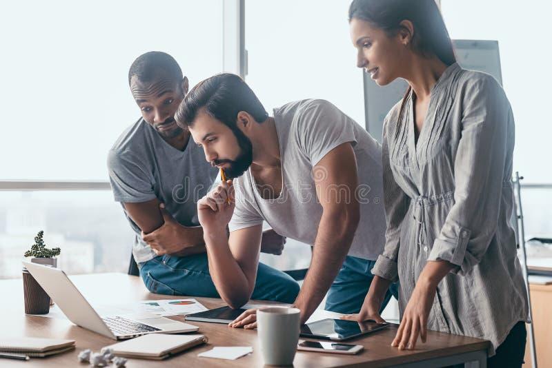 Mitarbeiter, die einen Laptop betrachten und über neuem Unternehmensplan sich besprechen Geschäftsteam, das zusammen herein an Co stockfoto