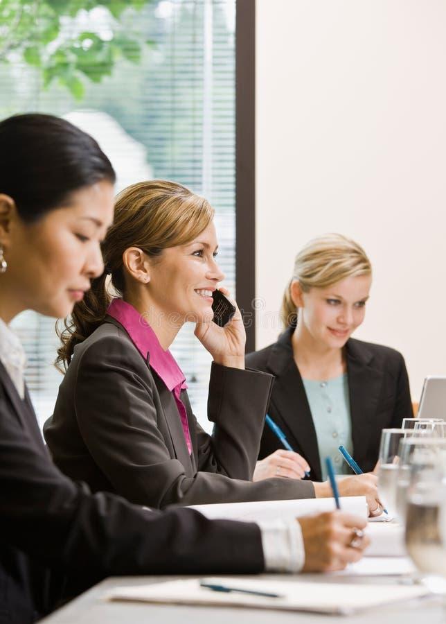 Mitarbeiter, die am Tisch im Konferenzsaal sich treffen lizenzfreies stockfoto