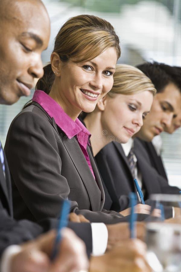 Mitarbeiter, die am Tisch im Konferenzsaal sich treffen stockbild