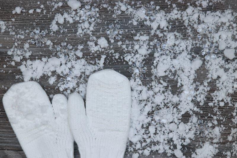 mitenes brancos no fundo de wi de madeira cobertos de neve das superfícies foto de stock royalty free