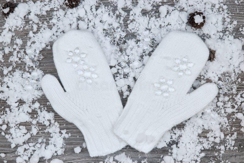 mitenes brancos no fundo de wi de madeira cobertos de neve das superfícies imagem de stock royalty free