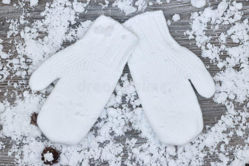 mitenes brancos no fundo de wi de madeira cobertos de neve das superfícies fotografia de stock royalty free