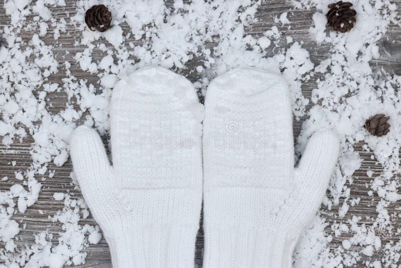 mitenes brancos no fundo de wi de madeira cobertos de neve das superfícies fotografia de stock