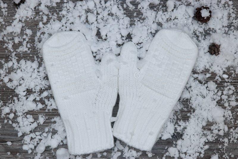 mitenes brancos no fundo de wi de madeira cobertos de neve das superfícies fotos de stock