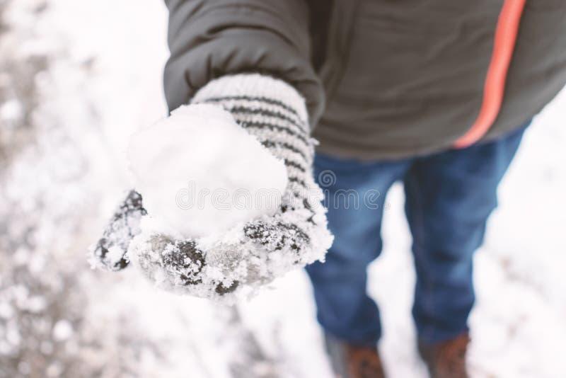 Mitenes vestindo de um menino, luvas de lãs que guardam uma bola de neve em sua mão, conceito exterior das atividades do inverno imagem de stock