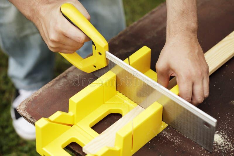 Miter Box. Man cutting a slat of wood using a saw and miter box royalty free stock image