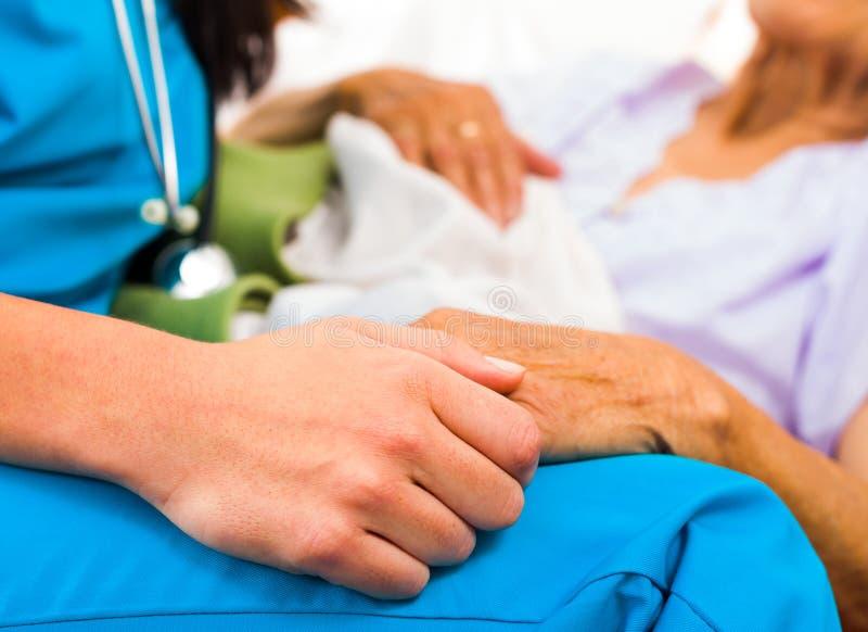 Mitfühlende Krankenschwester Holding Hands lizenzfreie stockfotografie