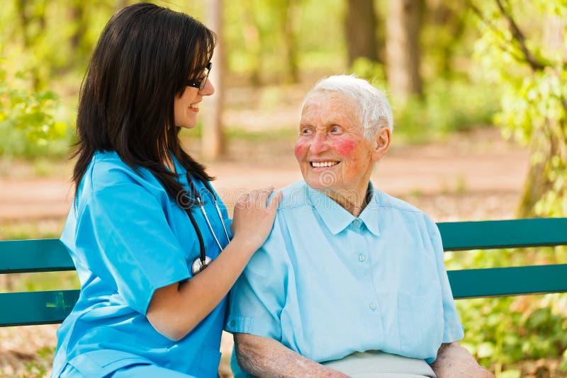 Mitfühlende Krankenschwester mit netter Dame stockbild