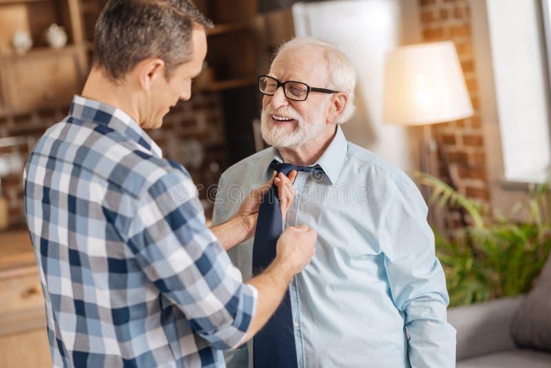 Mitfühlender Mann, der seinem älteren Vater hilft, seins zu binden Bindung stockbild