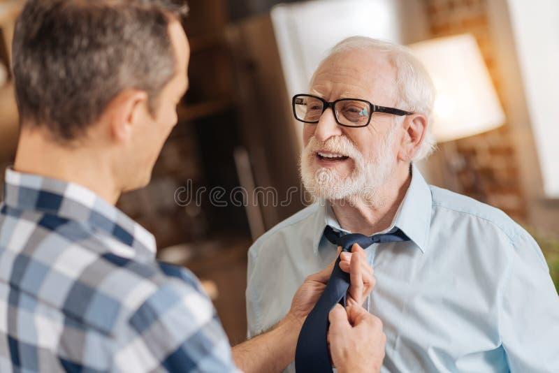Mitfühlender Sohn, der die Bindung seines älteren Vaters bindet stockbilder