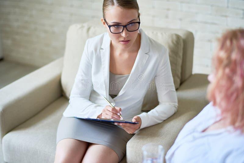 Mitfühlender weiblicher Psychiater Listening zum Patienten stockbild