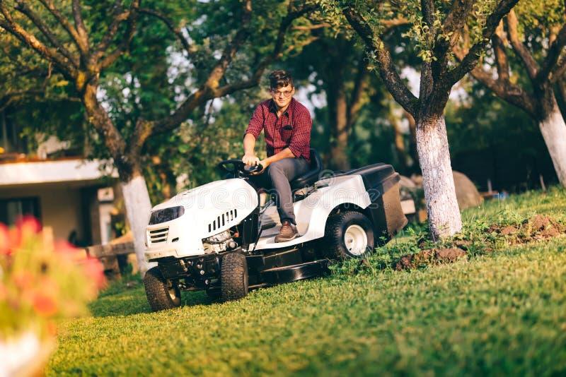 Mitfühlendes lawncare Konzept - hübsches Zutatgras des jungen Mannes im Garten unter Verwendung des Traktors lizenzfreie stockfotos