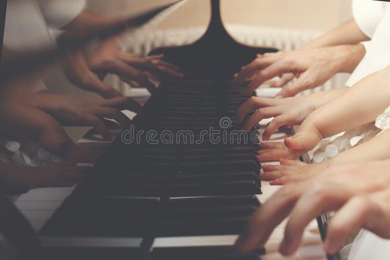 Mitglieder der dreiköpfigen Familie, die zusammen ein Klavier spielen stockbild
