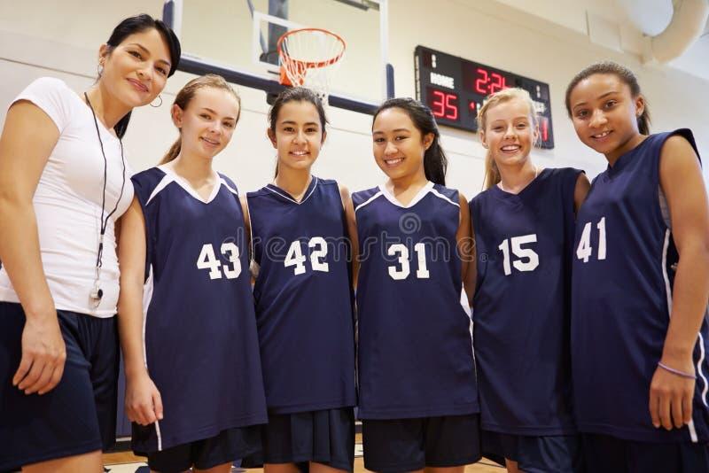 Mitglieder weiblichen Highschool Basketballs Team With Coach stockfotografie