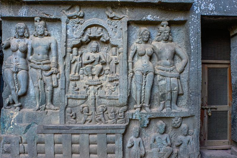 Mithuna couples on right of entrance of Chaitya hall. Intrusive Buddha image in between. Karla Caves,Lonavala. 15 May 2009 Mithuna couples on right of entrance stock image