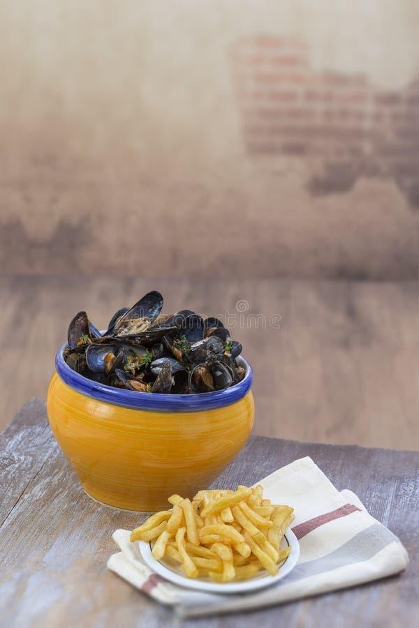 Mitilo comune francese con le erbe in una ciotola gialla con il ramekin di vetro delle patate fritte sui frutti di mare del tovag immagine stock libera da diritti