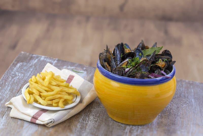 Mitilo comune francese con le erbe in una ciotola gialla con il ramekin di vetro delle patate fritte sui frutti di mare del tovag immagini stock libere da diritti