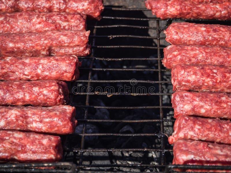 Mititei di Moldavo e cucinato sulla griglia nel fumo immagine stock