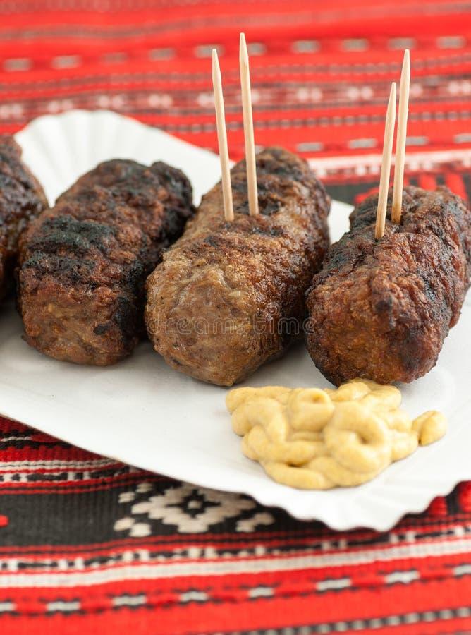 Mititei do romanian mici dos rolos de carne com mostarda imagem de stock