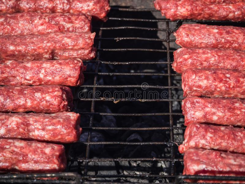 Mititei moldove et cuit sur le gril dans la fumée image stock