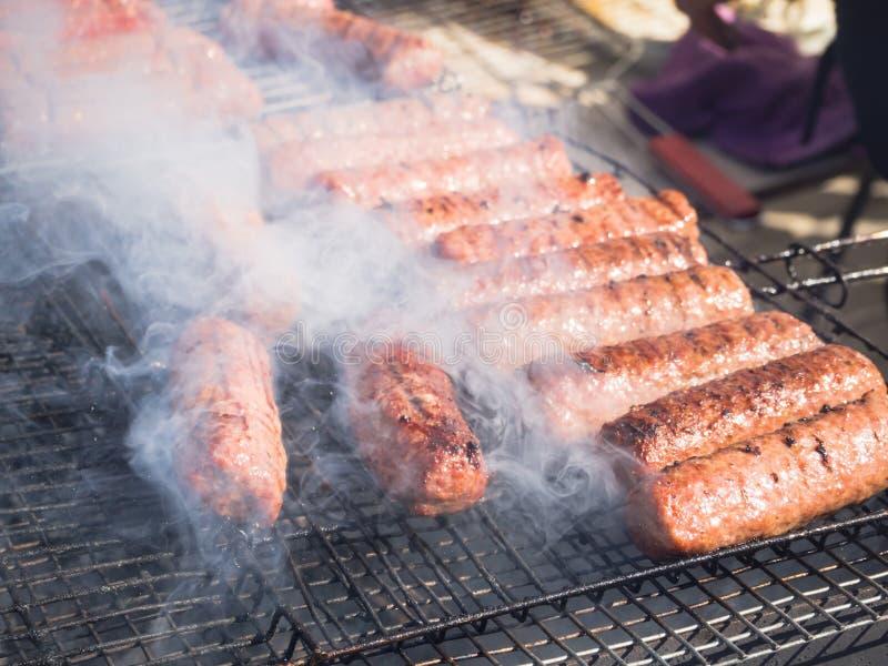 Mititei roumain et cuit sur le gril dans la fumée photographie stock libre de droits