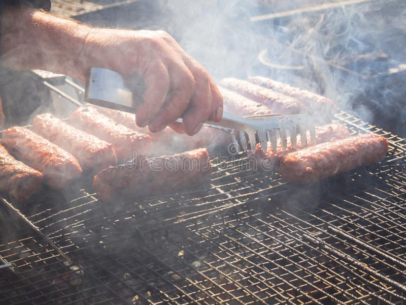 Mititei roumain et cuit sur le gril dans la fumée photos libres de droits