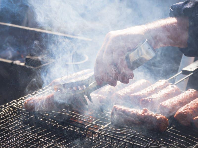 Mititei roumain et cuit sur le gril dans la fumée images stock