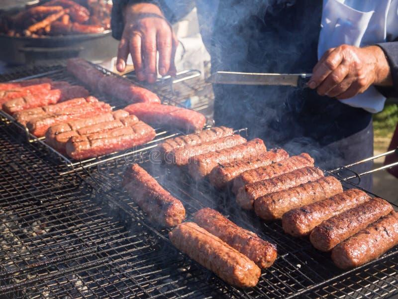 Mititei rumeno e cucinato sulla griglia nel fumo fotografia stock