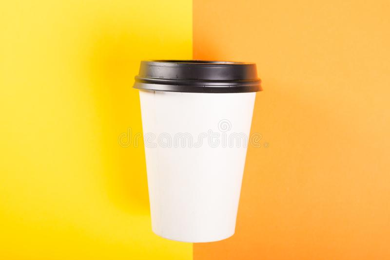Mitnehmerkaffeetasse auf orange und gelbem Hintergrund lizenzfreies stockfoto