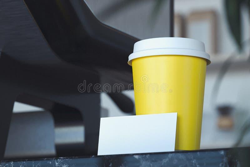 Mitnehmerkaffeetasse und leere Visitenkarte im hellen modernen Café Wiedergabe 3d lizenzfreie stockfotografie