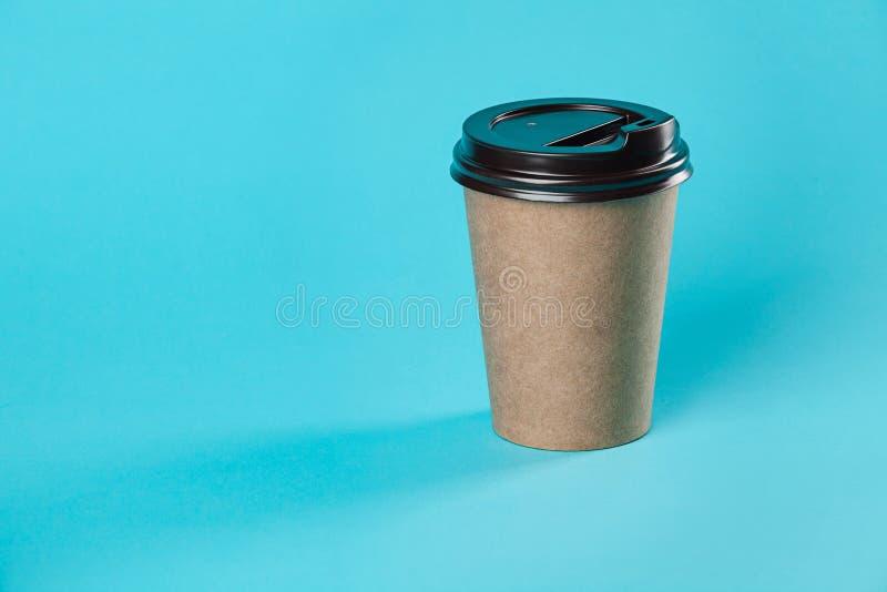 Mitnehmerpapierkaffeetassemodell lokalisiert auf blauem Hintergrund stockfotos