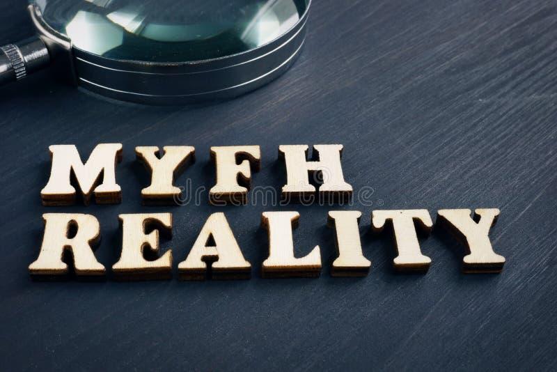 Mito e realtà di parola con la lente d'ingrandimento Notizie false fotografia stock libera da diritti