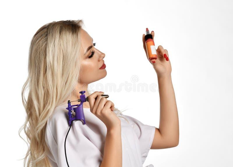 Mitragliatrice del tatuaggio della tenuta del cosmetologo dell'estetista della donna isolata su bianco immagini stock