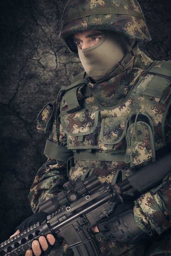 Mitragliatrice della tenuta dell'uomo del soldato delle forze speciali su un fondo scuro fotografia stock libera da diritti