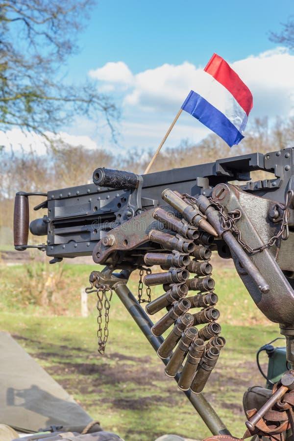 Mitragliatrice militare con le pallottole e la bandiera olandese immagine stock libera da diritti