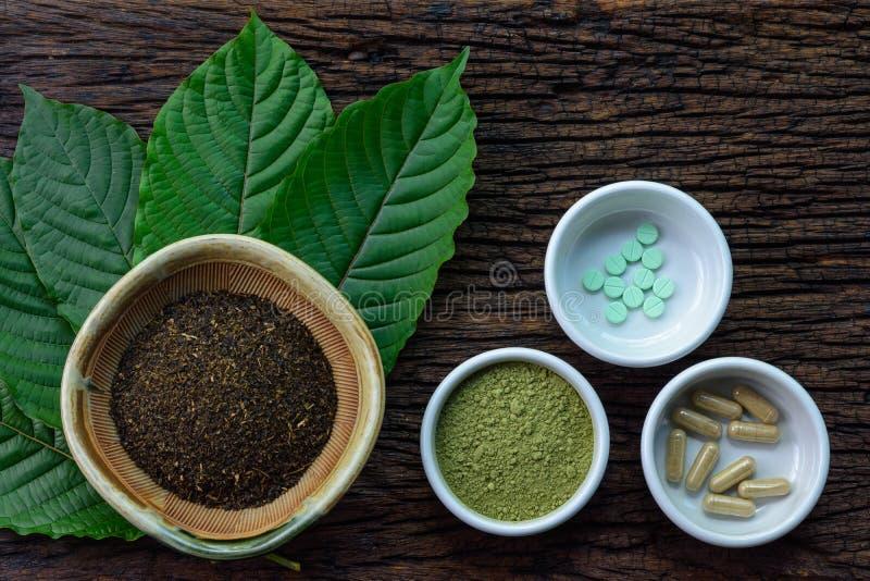 Mitragyna speciosa kratom离开与医学产品在粉末、胶囊和片剂在白色陶瓷碗在木纹理 免版税库存图片