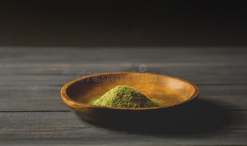 Mitragynina speciosa o polvere di Kratom in una ciotola di legno sulla tavola immagini stock libere da diritti
