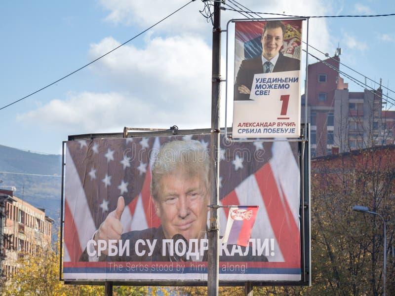 MITROVICA, KOSOVO - NOVEMBER 11, 2016: Servische affiche ondersteunend Donald Trump dichtbij een potrait van de Servische Eerste  stock foto's