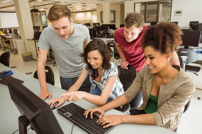 Mitschüler, die im Computerraum zusammenarbeiten stockfotos