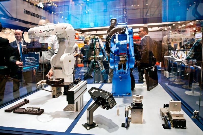 Mitsubishi och Yaskawa robotarmar på Schunk står på den Messe mässan i Hannover, Tyskland arkivbilder