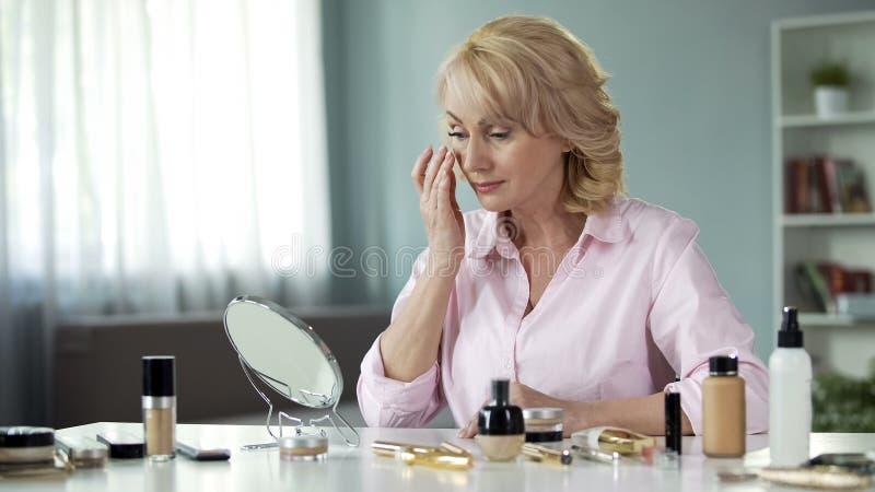 Mitt-ålder blond dam som framme applicerar anti--skrynkla kräm på framsida av spegeln royaltyfri bild