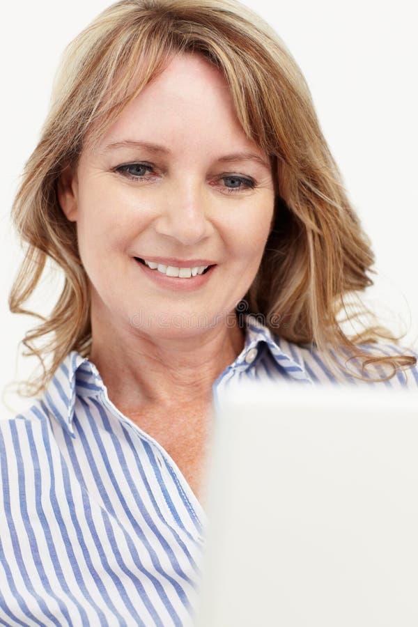Mitt- ålderaffärskvinna genom att använda bärbar dator fotografering för bildbyråer