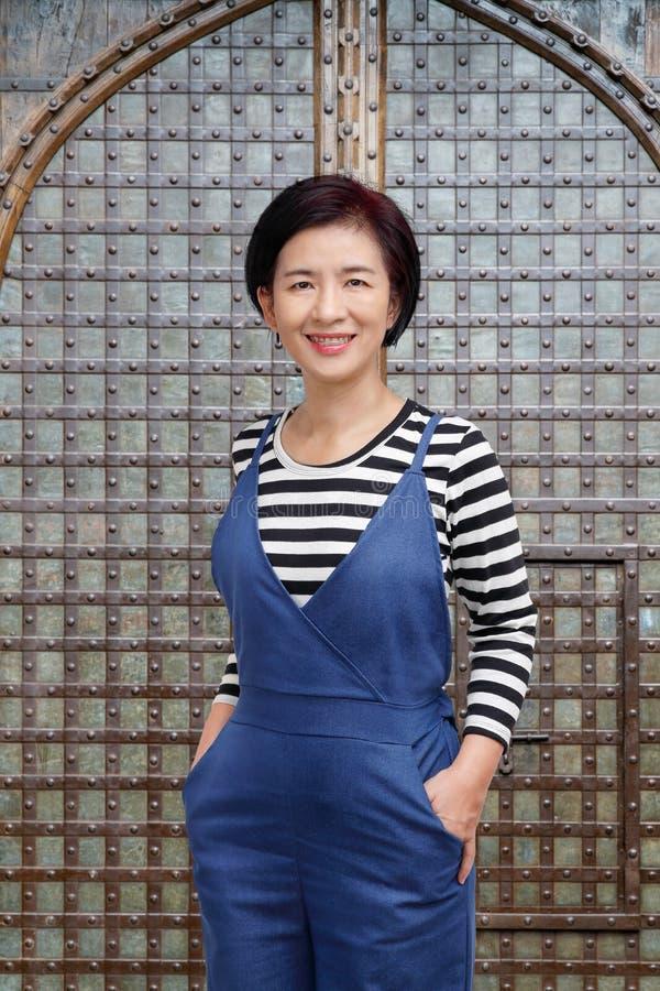 Mitt åldrades den asiatiska kvinnan som ler i tillfällig kläder royaltyfri fotografi