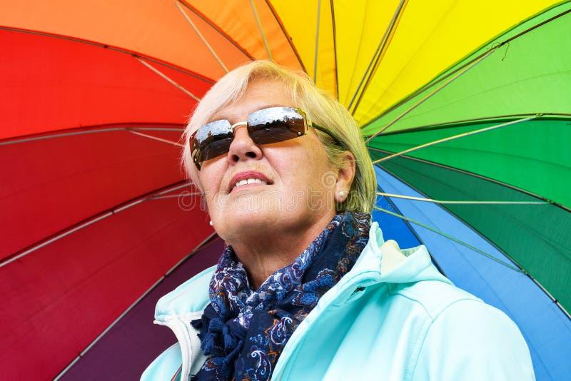 Mitt åldrades den gråa haired kvinnan som rymmer det färgrika paraplyet utanför på en solig dag arkivbilder