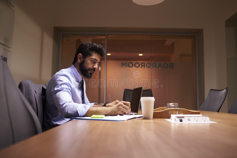 Mitt åldrades den latinamerikanska affärsmannen som sent arbetar i ett kontor arkivbild