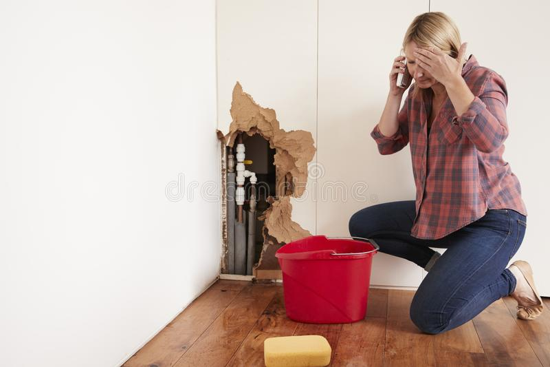 Mitt åldrades kvinnan med ett bristningsvattenrör som ringer för hjälp royaltyfri bild