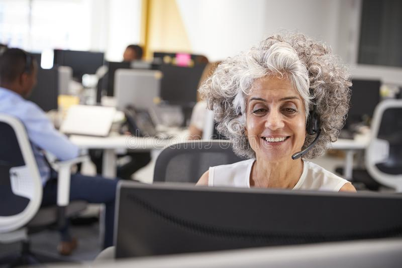 Mitt åldrades kvinnan som i regeringsställning arbetar på datoren med hörlurar med mikrofon fotografering för bildbyråer