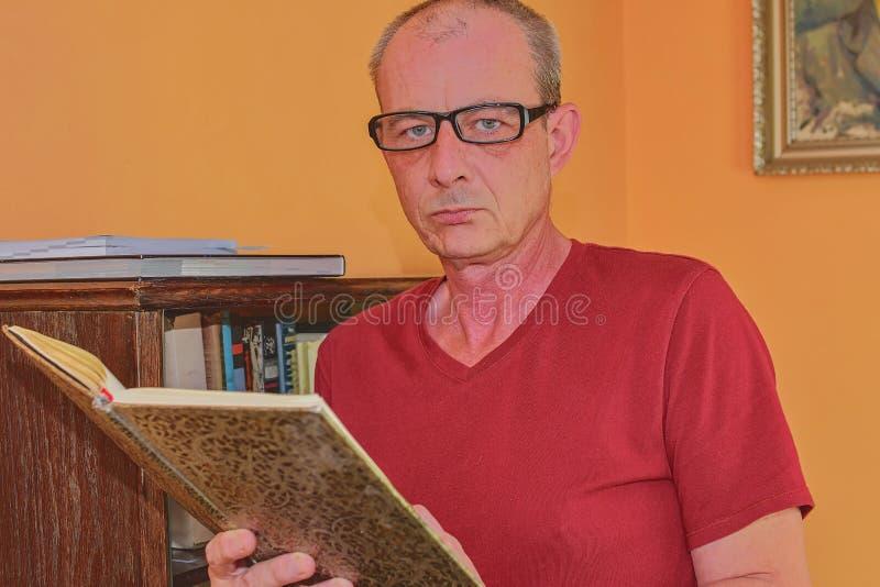 Mitt åldrades mannen är läseboken i vardagsrum Den mogna mannen står bredvid bokhyllan arkivfoto
