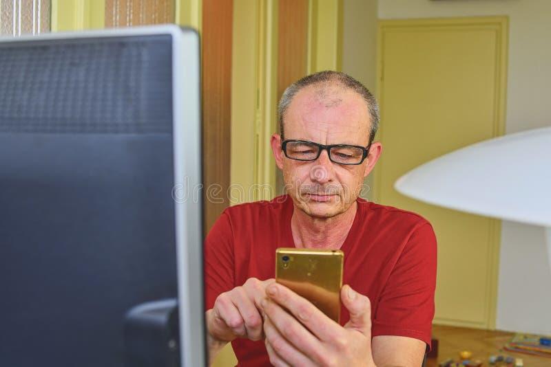 Mitt åldrades mannen med exponeringsglas som sitter på skrivbordet Mogna manen som använder mobil, ringer Högt begrepp Hemmastatt arkivfoto